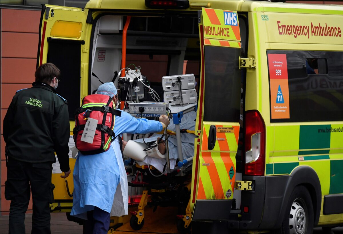 Medical workers move a patient between ambulances outside of the Royal London Hospital amid the spread of the coronavirus disease (COVID-19) pandemic, London