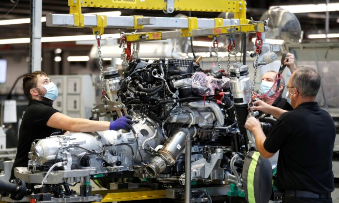 Technicians work on a Rolls-Royce engine prior to it being installed in a car on the production line of the Rolls-Royce Goodwood factory, near Chichester, Britain, on Sept. 1, 2020.  (Peter Nicholls/Reuters)