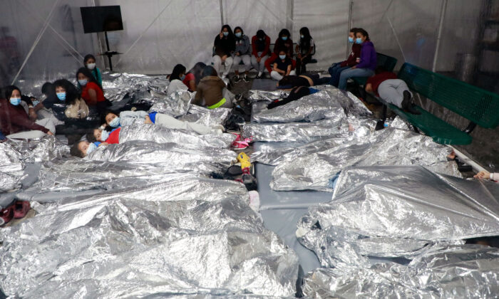 Unaccompanied minors sleep side by side on the floor at a temporary processing facility in Donna, Texas, on March 23, 2021. (CBP)