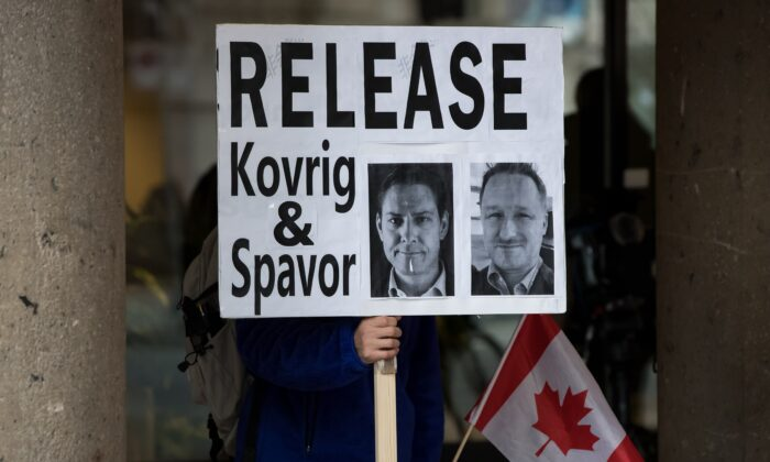 A man holds a sign bearing photographs of Michael Kovrig and Michael Spavor, who have been detained in China for more than a year, outside B.C. Supreme Court where Huawei chief financial officer Meng Wanzhou was attending a hearing, in Vancouver on Jan. 21, 2020. (Darryl Dyck/The Canadian Press)