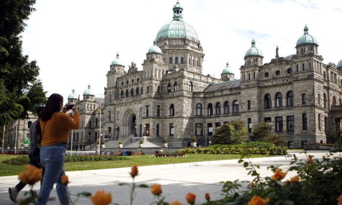 People walk past the B.C. legislature in Victoria on June 10, 2020. (The Canadian Press/Chad Hipolito)