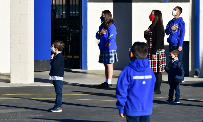 Students stand at attention as the national flag is raised at St. Joseph Catholic School in La Puente, Calif., on Nov. 16, 2020.  (Frederic J. Brown/AFP via Getty Images)