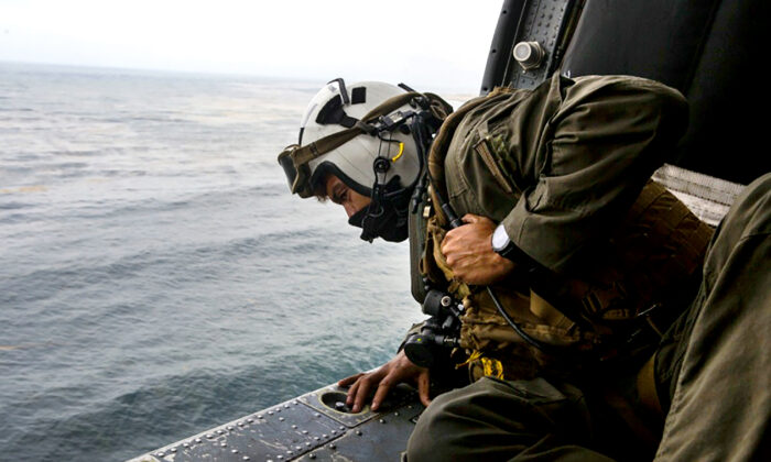 A Naval aircrewman looks out of a U.S. Navy helicopter while conducting search and rescue relief operations following an assault amphibious vehicle mishap off the coast of Southern California on July 30, 2020. (Lance Cpl. Mackenzie Binion/U.S. Marine Corps via AP)