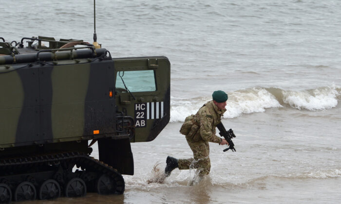 A Viking armored vehicle and a Royal Marine from 42 Commando take part in an exercise at Barry Buddon, simulating an attack in a hostile country in Carnoustie, Scotland, on April 12, 2013. (Jeff J Mitchell/Getty Images)