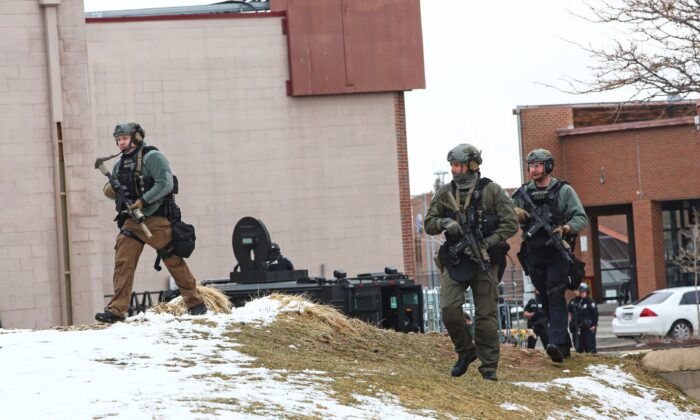 Law enforcement officers sweep the area outside of a King Soopers grocery store, which was the site of a shooting in Boulder, Colo., on March 22, 2021. (Kevin Mohatt/Reuters)
