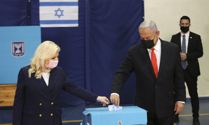 Israeli Prime Minister Benjamin Netanyahu and his wife Sara cast their ballots at a polling station as Israelis vote in a general election, in Jerusalem ,on March 23, 2021. (Ronen Zvulun/Pool via AP)