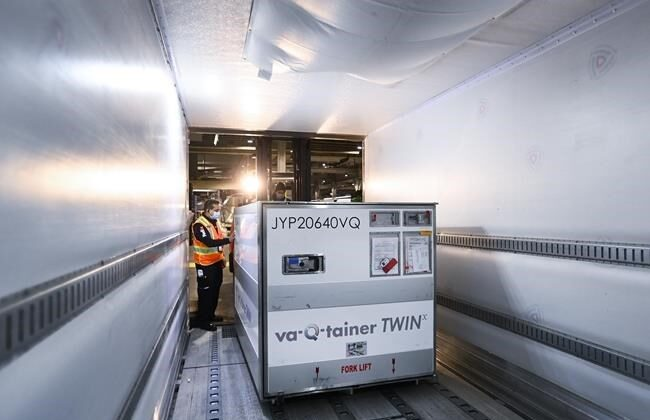 A FedEx worker loads the 255,600 doses of the Moderna COVID‑19 vaccine which came from Europe into a freezer trailer to be transported during the COVID-19 pandemic at Pearson International Airport in Toronto on March 24, 2021. (Nathan Denette / The Canadian Press)