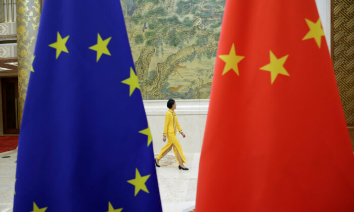 An attendant walks past EU and China flags ahead of the EU–China High-level Economic Dialogue at Diaoyutai State Guesthouse in Beijing on June 25, 2018. (Jason Lee/Reuters)