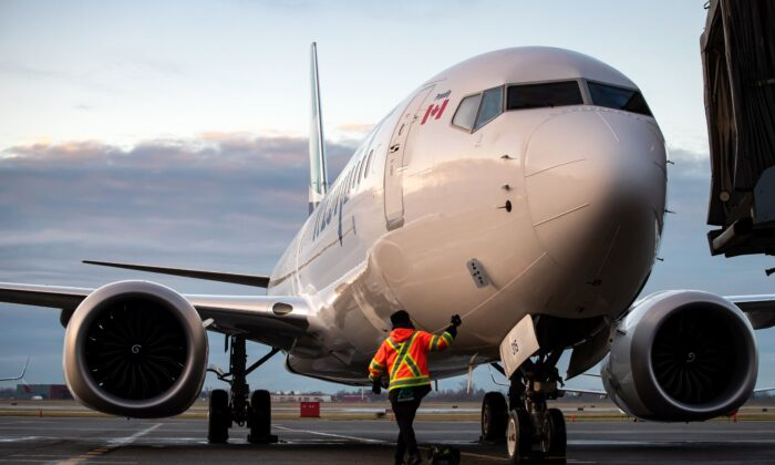 A ground worker approaches a WestJet Airlines Boeing 737 Max aircraft after it arrived at Vancouver International Airport on Jan. 21, 2021. (The Canadian Press/Darryl Dyck)