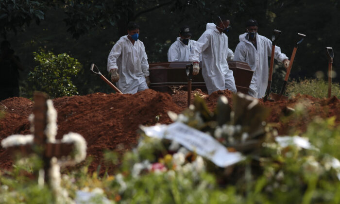 Cemetery workers carry the coffin of a victim of COVID-19 at the Vila Formosa cemetery in Sao Paulo, Brazil on March 23, 2021. (Miguel Schincariol/AFP via Getty Images)