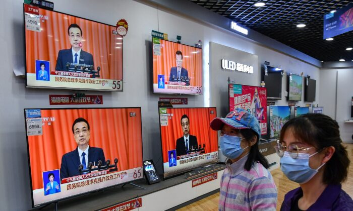 People walk past televisions broadcasting live coverage from CCTV. (AFP via Getty Images)