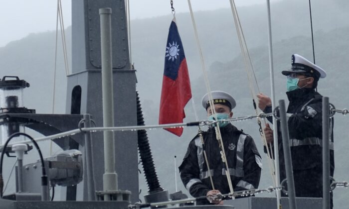 Two navy sailors raise Taiwan's national flag during an official ceremony at a shipyard in Su'ao, a township in eastern Taiwan's Yilan County, on Dec. 15, 2020. (Sam Yeh/AFP via Getty Images)