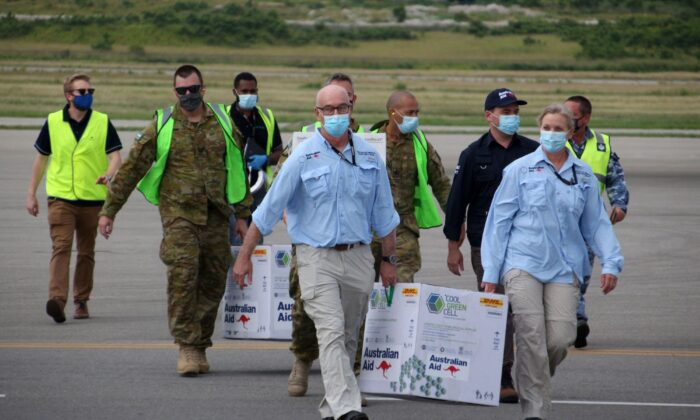 Australian officials carry boxes containing some 8,000 initial doses of the AstraZeneca vaccine at the Port Moresby international airport on March 23, 2021. (Andrew Kutan/Getty Images)
