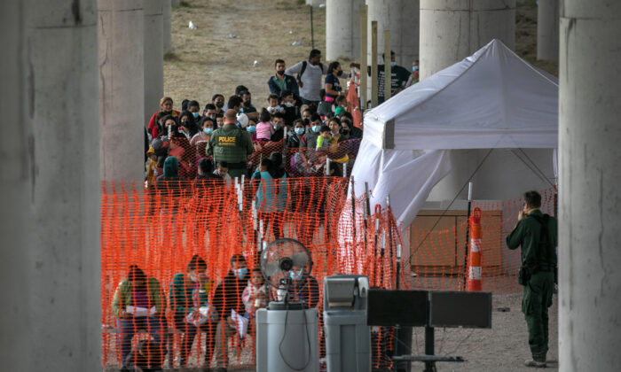 Illegal immigrants listen to instructions at an outdoor Border Patrol processing center under the Anzalduas International Bridge after crossing the Rio Grande from Mexico near Mission, Texas, on March 23, 2021. (John Moore/Getty Images)