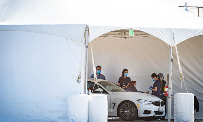 Medical workers prepare to administer a COVID-19 vaccination at a drive-thru site at Santa Ana College in Santa Ana, Calif., on Feb. 17, 2021. (John Fredricks/The Epoch Times)