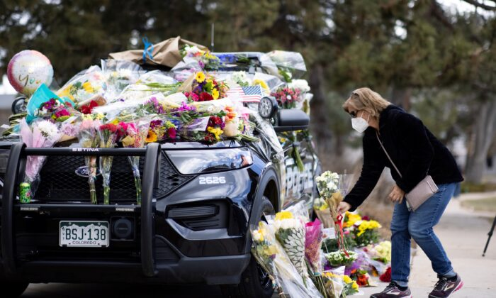 Karla Bielanski places flowers on the car of Officer Eric Talley, who was killed yesterday during a mass shooting in King Soopers grocery store, at Boulder Police Department, in Boulder, Colo., on March 23, 2021. (Alyson McClaran/Reuters)