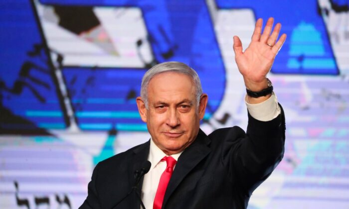 Israeli Prime Minister Benjamin Netanyahu waves to his supporters after the first exit poll results for the Israeli parliamentary elections at his Likud party's headquarters in Jerusalem on March 24, 2021. (Ariel Schalit/AP Photo)