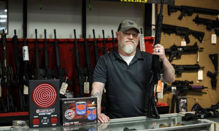 The owner of a gun shop stands behind the counter in White Sulphur Springs, W. Va., on Oct. 20, 2018. (Michael Mathes/AFP via Getty Images)