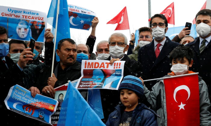 Ethnic Uyghurs and activists attend a protest against the visit of China's State Councilor and Foreign Minister Wang Yi to the Turkish capital in front of the Chinese Embassy in Ankara, Turkey on March 25, 2021. (Cagla Gurdogan/Reuters)