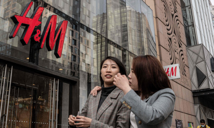 People walk past a store of Swedish clothing company H&M in Beijing on March 25, 2021. (Nicolas Asfouri/AFP via Getty Images)