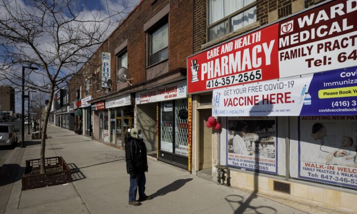 A pedestrian looks at a sign offering free COVID-19 vaccines at a pharmacy on an empty street in Toronto on March 14, 2021. (The Canadian Press/Cole Burston)