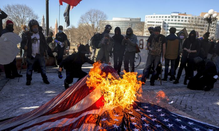 Members of the Communist Party USA and other anti-fascist groups burn an American flag on the steps of the Colorado State Capitol in Denver, Col., on Jan. 20, 2021. (Michael Ciaglo/Getty Images)