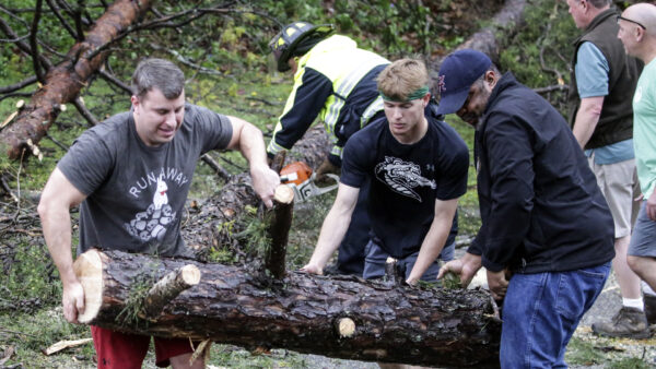 A firefighter works with residents to remove fallen trees