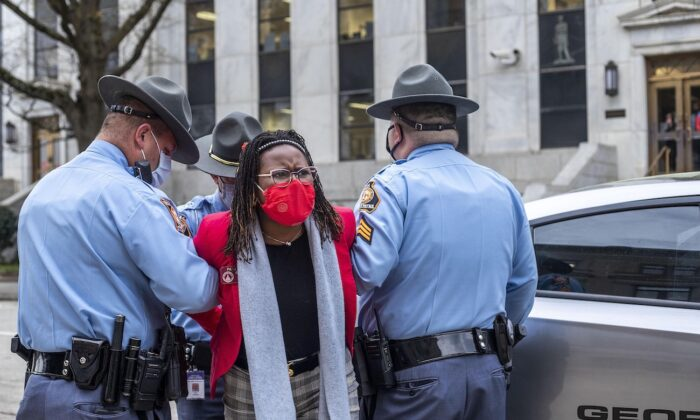Georgia State Rep. Park Cannon (D-Atlanta) is placed into the back of a Georgia State Capitol patrol car after being arrested by Georgia State Troopers at the Georgia State Capitol Building in Atlanta, Ga., on March 25, 2021. (Alyssa Pointer/Atlanta Journal-Constitution via AP)