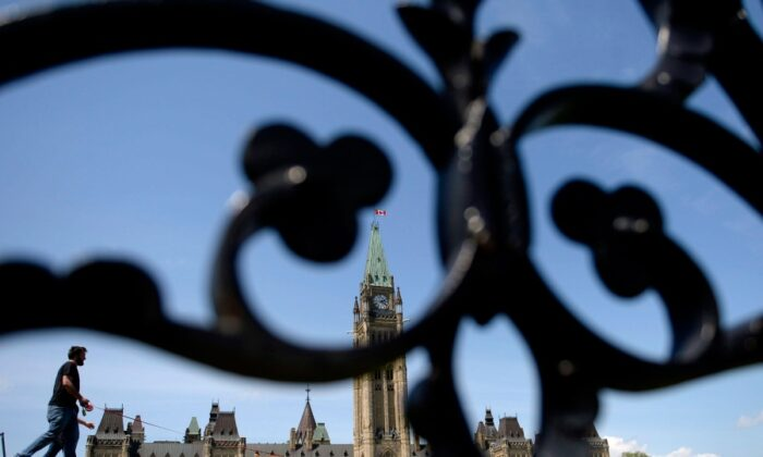 People walk on Parliament Hill on May 23, 2017. (Justin Tang/The Canadian Press)