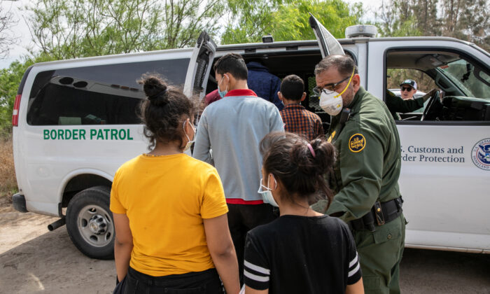Unaccompanied minors are loaded into a U.S. Border Patrol transport van after crossing the U.S.-Mexico border, in Hildalgo, Texas, on March 25, 2021. (John Moore/Getty Images)