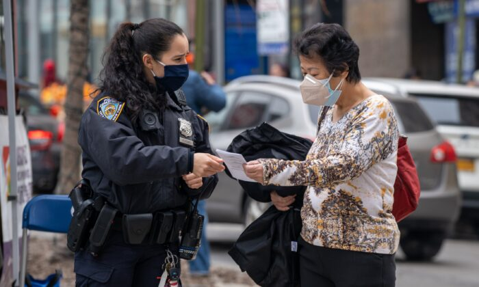 NYPD officers hand out information about hate crimes in Asian communities New York City, on March 17, 2021. (David Dee Delgado/Getty Images)