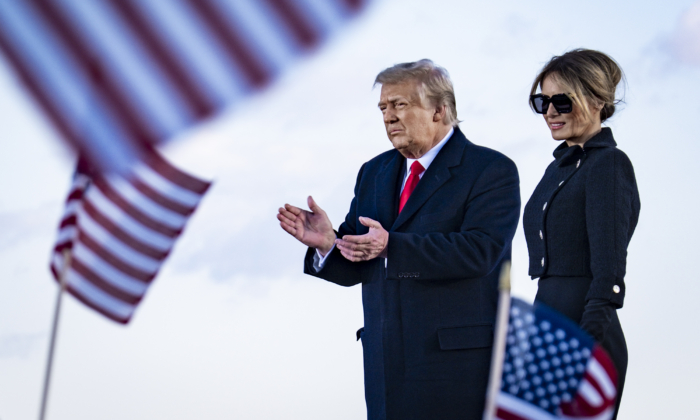 President Donald Trump and First Lady Melania Trump on stage after speaking to supporters at Joint Base Andrews before boarding Air Force One for his last time as president in Joint Base Andrews, Md., on Jan. 20, 2021. (Pete Marovich-Pool/Getty Images)