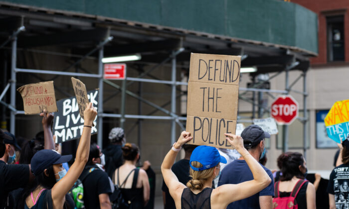 "A protester is holding a ""defund the police"" sign at a Black Lives Matter protest in Manhattan on July 13, 2020. (Chung I Ho/The Epoch Times)"