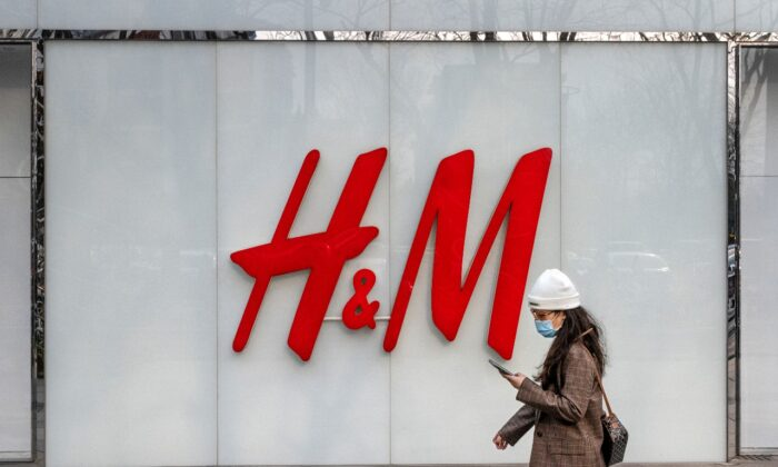 A woman walks by the flagship store of H&M in Beijing on March 25, 2021. (Kevin Frayer/Getty Images)
