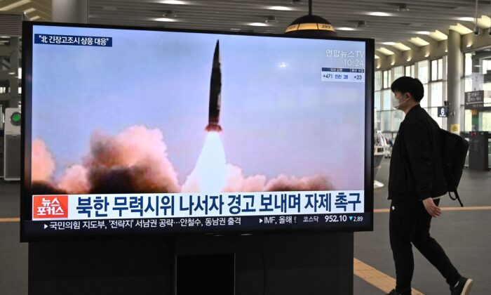 A man walks past a television screen at Suseo railway station in Seoul, showing news footage of North Korea's latest tactical guided projectile test, on March 26, 2021. (Jung Yeon-je/AFP via Getty Images)