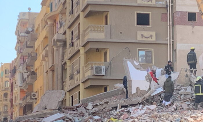 People inspect the area where a building was collapsed in Gesr al-Suez, Cairo, Egypt, on March 27, 2021. (Mai Shams El-Din/Reuters)