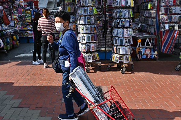 A woman is seen with a cart containing poster displays that slander Falun Gong, in Hong Kong, on March 25, 2021. (The Epoch Times)