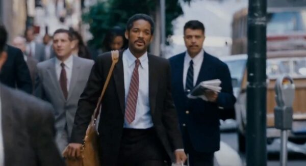 Will Smith in suit walking on crowded sidewalk