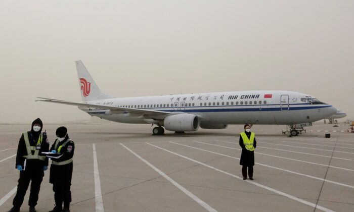 Staff members stand near a Boeing 737-800 airplane of Air China on the tarmac of Beijing Capital International Airport, which is shrouded in dust as the city is hit by a sandstorm, in Beijing, China, March 28, 2021. (Carlos Garcia Rawlins/Reuters)