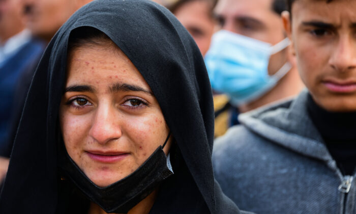 A woman reacts during a a mass funeral for Yezidi victims of the Islamic State (ISIS) group in the northern Iraqi village of Kojo in Sinjar district, on Feb. 6, 2021. (Zaid al-Obeidi/AFP via Getty Images)