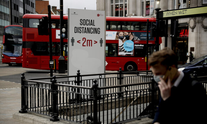 A large social distancing sign is displayed next to an entrance down into Oxford Circus underground train station in central London on March 26, 2021.(Matt Dunham/AP Photo)
