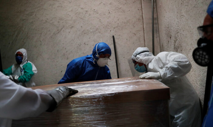 Funeral and crematorium employees work on a coffin carrying the body of a person who died from the coronavirus disease at San Isidro crematory in Mexico City, Mexico, on May 21, 2020. (Carlos Jasso/Reuters)