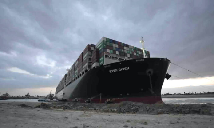 Tug boats and diggers work to free the Panama-flagged, Japanese-owned Ever Given, which is lodged across the Suez Canal, Egypt, on March 28, 2021. (Suez Canal Authority via AP)