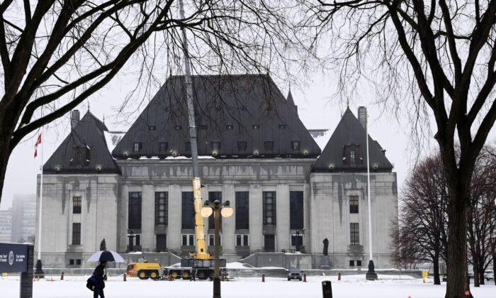 A pedestrian walks past the Supreme Court of Canada in Ottawa on Nov. 26, 2020. (The Canadian Press/Sean Kilpatrick)