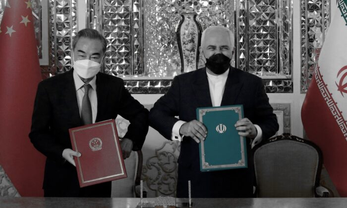 Iranian Foreign Minister Mohammad Javad Zarif (R) and his Chinese counterpart Wang Yi, pose for a picture after signing an agreement in Tehran, Iran, on March 27, 2021. (-/AFP via Getty Images)