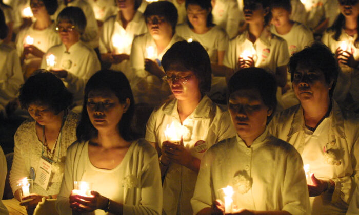 Falun Gong practitioners hold candles during a candlelight vigil in Washington, D.C., July 19, 2001. (Alex Wong/Getty Images)