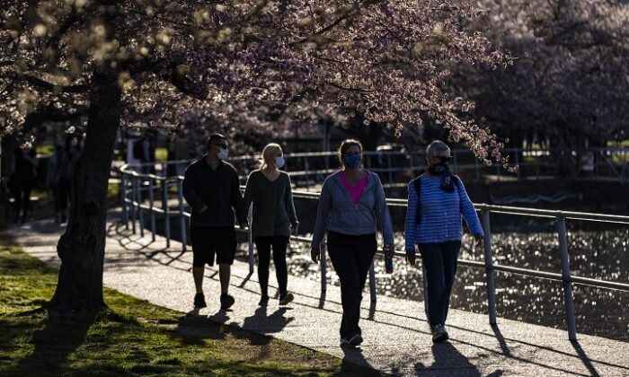 People walk among blooming cherry trees along the Tidal Basin in Washington, on March 27, 2021. (Samuel Corum/Getty Images)