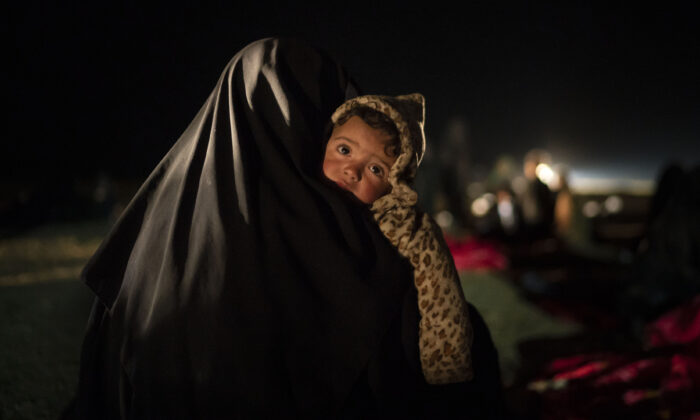 A woman carries her baby at a screening center run by U.S.-backed Syrian Democratic Forces after being evacuated out of the last territory held by Islamic State militants, outside Baghouz, Syria, on Feb. 25, 2019. (Felipe Dana/File/AP Photo)