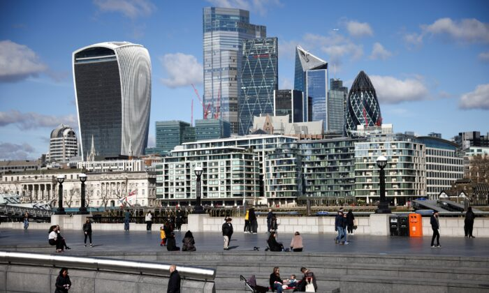 The City of London financial district can be seen as people walk along the south side of the River Thames in London on March 19, 2021. (Henry Nicholls/Reuters)