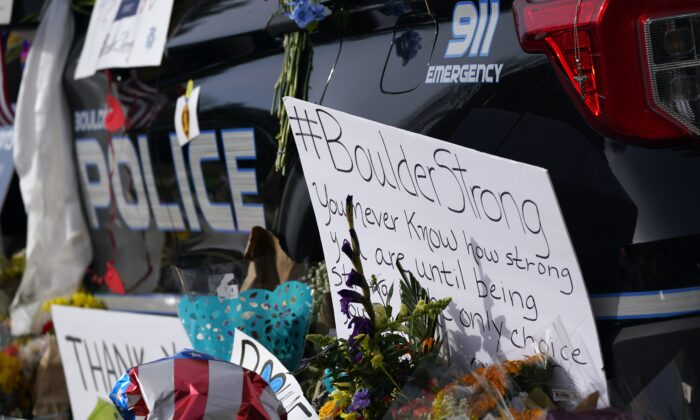 Signs, floral bouquets and tributes stand along side a police cruiser parked in front of the Boulder, Colo., Police Department in honor of fallen officer Eric Talley, who was one of 10 victims in a mass shooting at a King Soopers grocery store, before a news conference about the ongoing investigation outside police headquarters in Boulder, Colo., on March 26, 2021. (David Zalubowski/AP Photo)